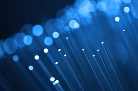 fiberoptics: Close up on the ends of many illuminated blue fiber optic strands with black background. Focus on foreground. Stock Photo