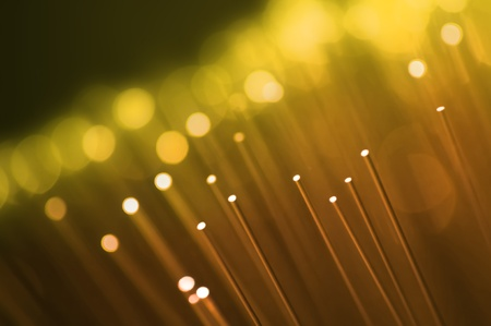 Close up on the ends of many illuminated golden fiber optic strands with dark background. Focus on foreground. Stock Photo - 11151940