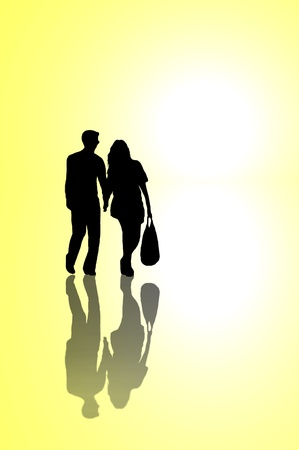 sillhouette: A silhouetted young couple walking on reflective surface towards a bright light with yellow background. Stock Photo