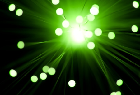 Photograph capturing the blurred ends of many illuminated green fiber optic strands emerging from a central ilght source with black background  photo