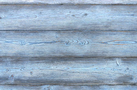 Vintage background composed of planks of blue color on which the paint for a long period of time fell into disrepair and clearly visible