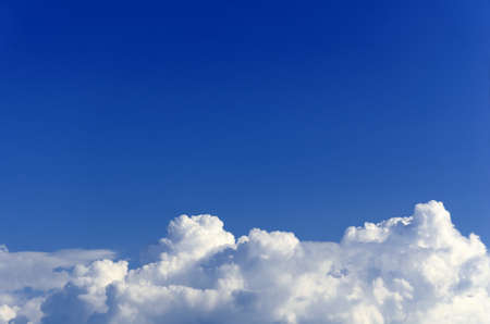 background for the text consisting of white fluffy clouds on a background of boundless blue sky