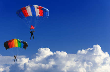 two parachutists soar on colorful parachutes across the boundless blue sky against the background of white fluffy clouds Banque d'images