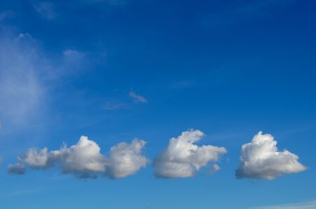 three white fluffy clouds slowly move against the background of the boundless blue sky
