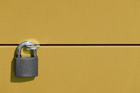 a steel colored metal padlock securely connects two gold colored metal doors
