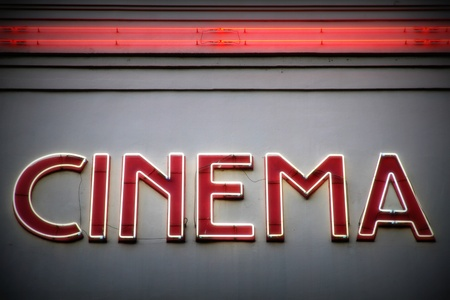 home cinema: Cinema advertising red neon sign on a wall Stock Photo