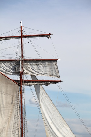 Mast and canvas sails of a sailing ship photo