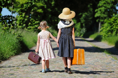 Two little girls walking with her luggage at a tree-lined road, seen from the back Stock Photo