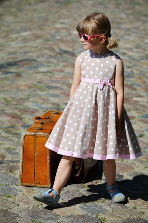 petticoat: Little girl with polka-dotted dress stands pretty cool on the street Stock Photo
