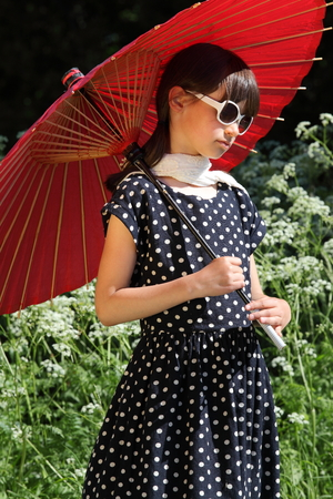 dreamy eyed: Retro dressed child girl holding a red asian style paper sunshade Stock Photo