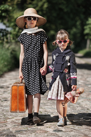 french model: Two retro styled child girls walk together at a road in the countryside Stock Photo