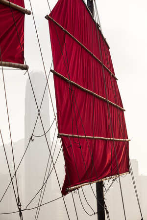 Hongkong traditional red canvas sail, rigging and mast of an old boat and modern skyline at the background photo