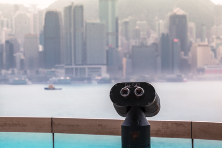 Binoculars at a lookout point with the harbor and cityscape of Hong Kong