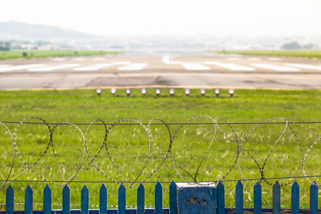 Barbwire fence at an airport runway area photo