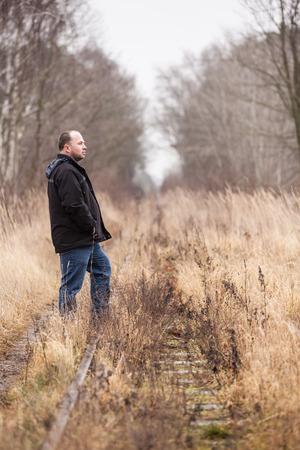 Middle aged man is walking along abandoned railway tracks Stock Photo