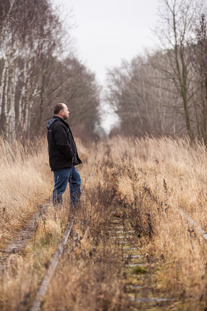 Middle aged man is walking along abandoned railway tracks photo