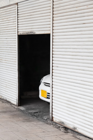 Open roller door of a garage with the front part of a car inside that looks out photo