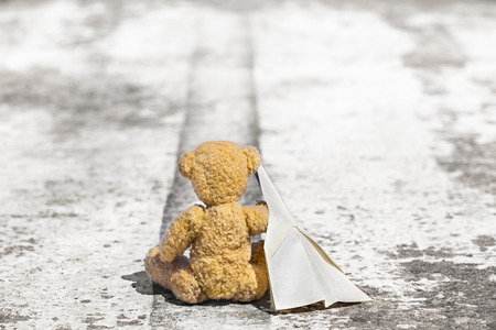 tar paper: Little teddy bear is sitting at an asphalt runway with a paper plane on his arm