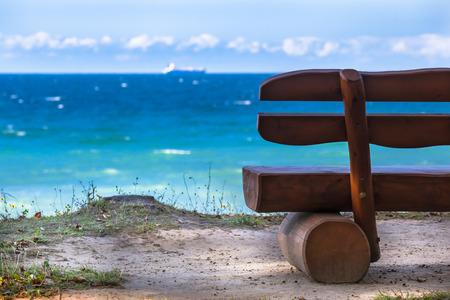 Half of a bench standing at a cliff at the sea photo