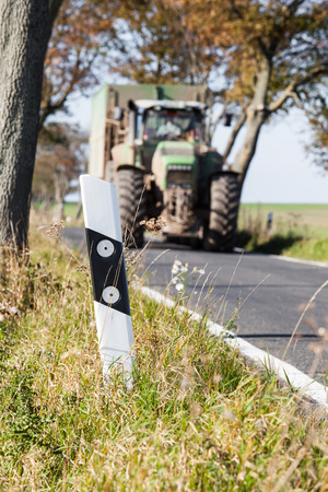 one lane sign: Rural street reflecting road marking pylon and a tractor at the background
