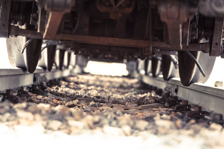 overrun: View inside a railroad track under a heavy steam locomotive with many wheels