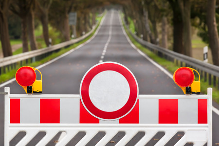 barrera: Barrera de la calle de color rojo y blanco en una carretera vacía Foto de archivo