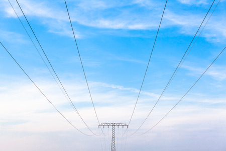 power cables: Electricity power cables and metal pylon construction in front of cloudy blue sky