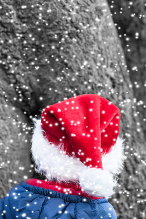 imp: Little christmas elf in front of a huge tree in the snowy forest Stock Photo