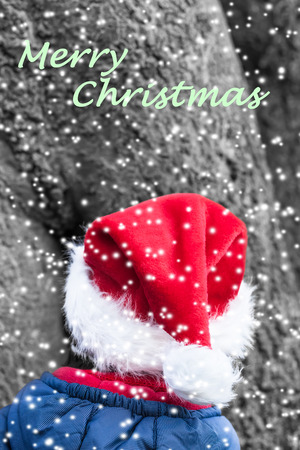 imp: Merry christmas wish with little christmas elf in front of a huge tree in the snowy forest Stock Photo
