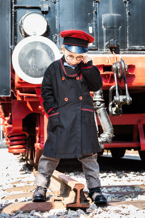 inspector kid: Nostalgic little child boy railroad conductor stand in front of a steam locomotive looking down and wondering about the end of the track