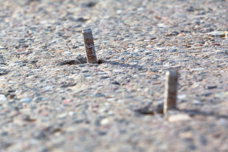 footing: Pair of screws partly inside a concrete slab foundation