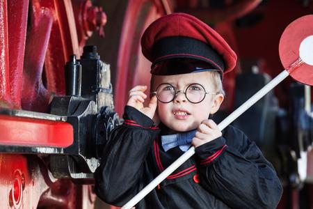 locomotora: Retrato de un pequeño muchacho lindo del niño con la expresión facial molesto como conductor de ferrocarril nostálgico y metalrimmed tapa de vidrios y el disco de señalización