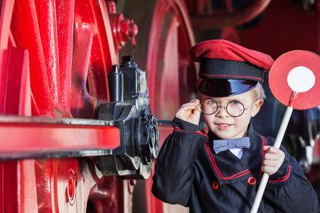 tren: El ni�o peque�o ni�o como conductor de ferrocarril nost�lgico con el casquillo y el disco de se�alizaci�n junto a grandes ruedas de una locomotora de vapor Foto de archivo