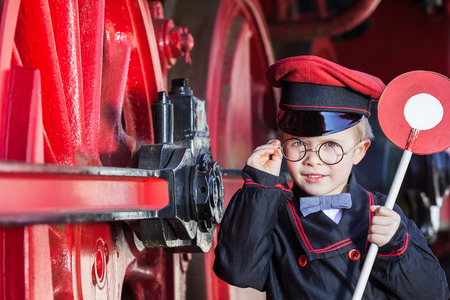 Little child boy as nostalgic railroad conductor with cap and signaling disk beside large wheels of a steam locomotive