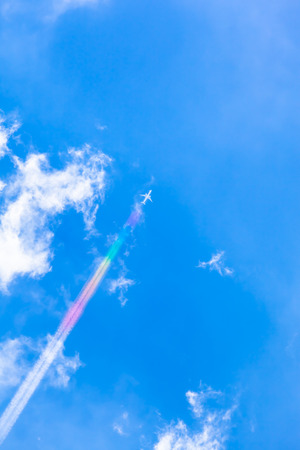 contrail: Airplane with contrail like a colorful rainbow at the blue cloudy sky