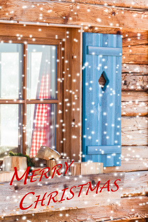 textual: Snowy window detail of a bavarian alps wooden mountain hut with textual holiday message