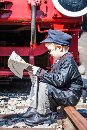 lunch hour: Small child boy as nostalgic locomotive driver sitting at the railway track and reading a newspaper at lunch hour