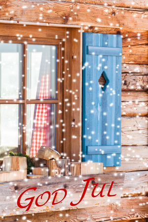 textual: Snowy window detail of a bavarian alps wooden mountain hut with textual holiday message in swedish language God Jul Stock Photo
