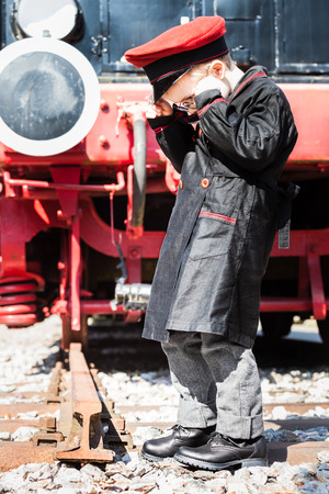 inspector kid: Nostalgic little child boy railroad conductor stand in front of a steam locomotive, looking down and wondering about the end of the track Stock Photo