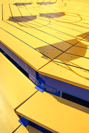 chairoplane: Detail of yellow wooden stairs of a swing carousel and shadows of the swing seats on the planks