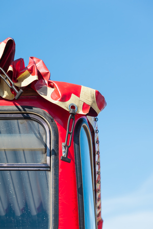 tarpaulin: Detail of red bus windows with tarpaulin opened roof in front of blue sky copy space Stock Photo