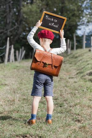 古着と彼の革ランドセルに赤いベレー帽帽子の若い学校の男の子は戻って小さな黒板を保持本文 - 学校に戻って彼の頭の上 写真素材