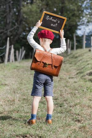 古着と彼の革ランドセルに赤いベレー帽帽子の若い学校の男の子は戻って小さな黒板を保持テキスト - 学校で彼の頭の上 写真素材