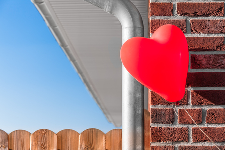 owning: Part of a brick build house with water drain pipe and board fence and a floating red heart shaped balloon at the corner as a dream of owning a house