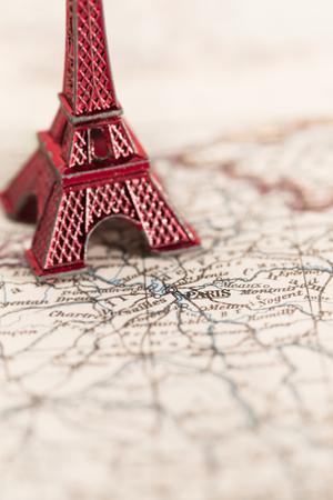 copy space: Paris name at a map with red Eiffel tower miniature blurred copy space