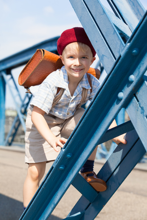 steel girder: Retro styled little boy with shadow at the half of his face at the way to - from school wear satchel, suspenders, shirt, shorts and red beret hat, climb at a blue steel girder Stock Photo