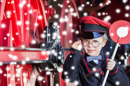 inspector kid: Little child boy in winter as nostalgic railroad conductor beside large wheels of a steam locomotive with snowflakes and copy space
