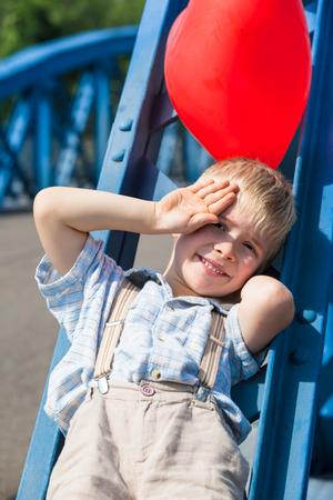 steel girder: Young small boy use his hand as sunshade and resting at the blue steel girder of a bridge with his red balloon Stock Photo