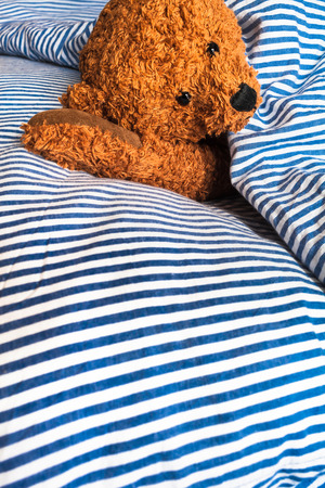 Cute cuddly teddy bear resting with the head on his arm in white and blue striped bedclothes (copy space)