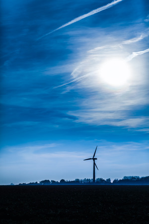 industry moody: Silhouette of wind generator and horizon with dramatic twilight sky